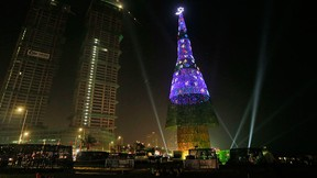 An enormous artificial Christmas tree is seen lit up after its unveiling in Colombo, Sri Lanka, Saturday, Dec. 24, 2016. (AP Photo/Eranga Jayawardena)