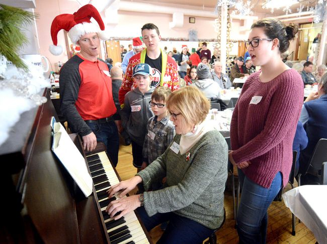 Joining pianist Mary Anne Lealess to sing carols for guests at the annual Christmas dinner at St. James' Anglican Church on Sunday are Phil Meadows, at left, with his two sons Cole, 11, and Nate, 6, and nephew Kurt Watson, 15, and, at right, Abby Cronin. SCOTT WISHART/The Beacon Herald