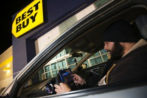 Martin Norry sits in his car and watches a movie on a tablet as he waits for the Best Buy in South Edmonton Common to open, in Edmonton Sunday Dec. 25, 2016.David Bloom/Postmedia