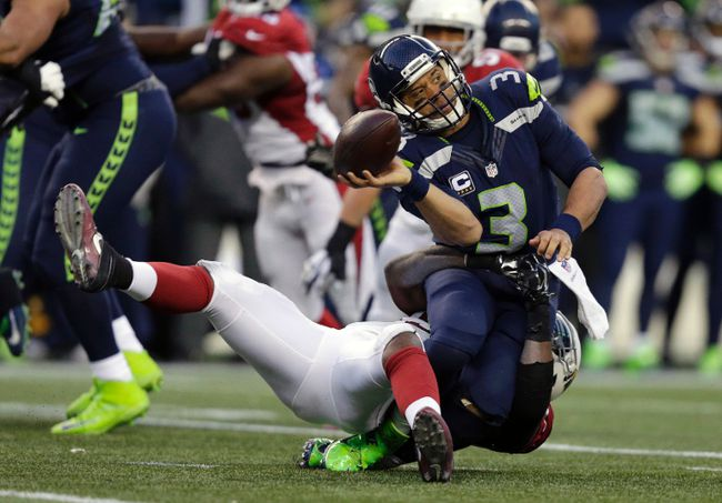 Seattle Seahawks quarterback Russell Wilson (3) is tackled by Arizona Cardinals' Sio Moore as he releases the ball in the second half of an NFL football game, Saturday, Dec. 24, 2016, in Seattle. (AP Photo/John Froschauer)