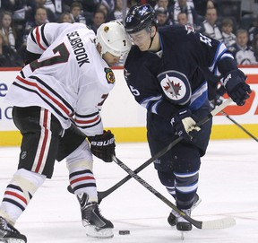Winnipeg Jets centre Mark Scheifele (right) and Chicago Blackhawks defenceman Brent Seabrook butt heads. The Jets play the Hawks Tuesday night in Chicago. (Kevin King/Winnipeg Sun file photo)