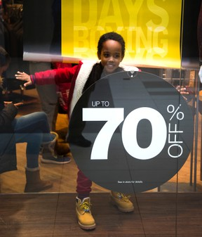 Henok Bekele, 5 escapes for his sister's who were minding their phones, into the display window of a men's clothing shop at White Oaks Mall in London, on Boxing Day. Bekele, froze like a mannequin once he was spotted. (MIKE HENSEN, The London Free Press)