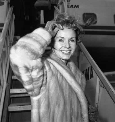 In this March 6, 1959, file photo actress Debbie Reynolds boards an airliner in New York en route to Spain where she will film a new picture. (AP Photo/John Rooney, File)