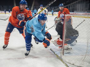 Ryan Nugent-Hopkins is pushed from behind by Brandon Davidson as the Edmonton Oilers practice at Rogers Place leading up to a New Year's Eve game against the Vancouver Canucks. (Shaughn Butts)