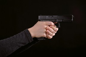 A woman holds a gun in this file photo. (Getty Images)
