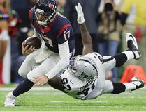 Texans quarterback Brock Osweiler (17) scrambles for a first down against Raiders defensive end Mario Edwards (97) during first half AFC Wild Card action in Houston on Saturday, Jan. 7, 2017. (Eric Gay/AP Photo)