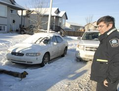 Senior peace officer Mario Paradis watches as Nolan Delmas of AB Towing hooks up a car slated for removal from a snow route on 88A Street Thursday, December 15, 2011 in Grande Prairie, Alberta. City enforcement services has begun cracking down on illegal parking in snow routes, which are declared seasonal no parking zones in Grande Prairie. DAN ILIKA/DAILY HERALD-TRIBUNE/Postmedia Network File Photo