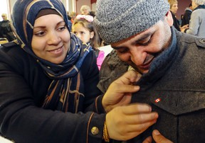 LUKE HENDRY/THE INTELLIGENCER  Raghda Al Mansour affixes a Canadian flag pin to the jacket of her husband, Mohamed Hamada, in the Islamic Society of Belleville's mosque Sunday. They and their three young children arrived in the city Dec. 28.