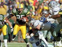 Green Bay Packers running back Dorsey Levens (L) breaks through the Dallas Cowboys defensive line for a first down, as Dallas Cowboys defensive tackle Chad Hennings (C) misses the tackle, during the first quarter of the Nov. 23, 2016, game at Lambeau Field, in Green Bay, Wis. (VINCENT LAFORET/AFP/Getty Images)