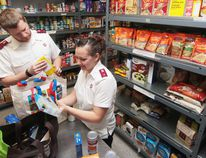 KEVIN RUSHWORTH HIGH RIVER TIMES/POSTMEDIA NETWORK. Lieutenants Cory and Kelly Fifield, with the Salvation Army Foothills, check food items before putting them on the shelves at High River's food bank.
