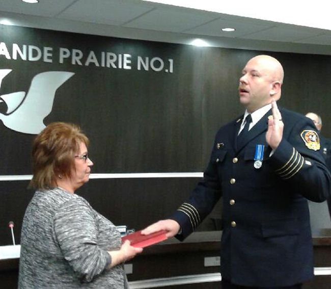 Trevor Grant takes the oath as the new chief for the County of Grande Prairie's Regional Fire Service as Sherry Green, the county commissioner of oaths, holds the Bible, on Monday.