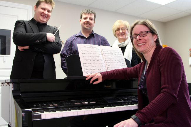 Angela Garwood-Touw, concert master with the Timmins Symphony Orchestra, sits in front of a piano for this photo with conductor Joshua Wood, publicity coordinator Luc Martin and board member Karen Bachmann, to promote their new season of concerts.