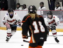 Peewee female Rockies players Kristina Krywolt (L) and Rowan Bremner attack the Thunder defense and net during the Female Rockies Tournament. Cochrane beat Brooks in the bronze medal game.