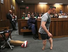 Oscar Pistorius's prosthetics lie on the floor as he walks on his amputated legs during argument in mitigation of sentence by his defense attorney Barry Roux in the High Court in Pretoria, South Africa, on June 15, 2016. (Siphiwe Sibeko via AP, Pool, File)