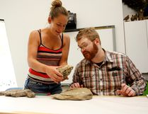 Melissa Hedberg, left, came up all the way from Dawson Creek to show assistant curator Derek Larson some of the fossils she found during the last Fossil ID Day event at the Philip J Currie Dinosaur Museum in August. The museum will be running another event this Saturday from 1-3 p.m. DHT file photo