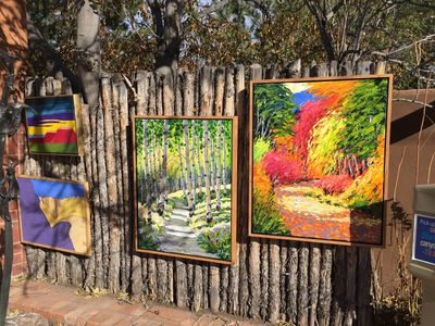 Colourful paintings displayed along a rustic fence at Bill Hester Fine Art on Santa Fe's artsy Canyon Road. ROBIN ROBINSON/TORONTO SUN