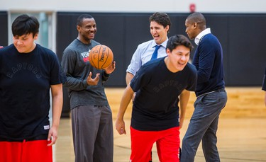 Canadian Prime Minister Justin Trudeau (middle) chats with Toronto Raptors head coach Dwane Casey (left) Raptors president and general manager Masai Ujiri, while they watch visiting students of La Loche Community School in Saskatchewan on the basketball court at the BioSteel Centre, where the Toronto Raptors practice, in Toronto, Ont. on Friday January 13, 2017.  Masai Ujiri, Toronto Raptors president and general manager, hosted a group of 10 kids, plus two teachers, from La Loche, Saskatchewan. Ernest Doroszuk/Toronto Sun/Postmedia Network