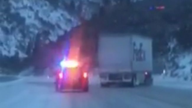 A California Highway Patrol officer filmed a big rig that had jackknifed at the top of a slippery highway do a controlled slide about a mile downhill until the next exit. (Facebook screengrab)