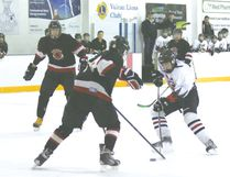 Vulcan bantam Hawk Scott Donovan is met by an opposing Siksika Warrior player as he makes his way to Siksika's goal during a game Friday evening at the Vulcan District Arena.