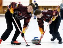 Lead Devon Weese, left, and second Oliver Campbell of the Chatham Granite Club under-21 men's team sweep during an exhibition match against the club's under-18 team at the Chatham Granite Club recently. (MARK MALONE/The Daily News)