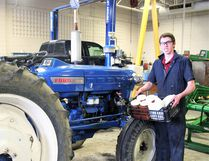 St. Anne's student Evan Krebs in front of his tractor that he reconfigured to run on biofuels soybean and canola oil. (Justine Alkema/Clinton News Record)