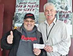 With his trademark thumb up, Danny Kleinsasser presents a cheque for $200 to Siloam Mission CEO Jim Bell. (Facebook)