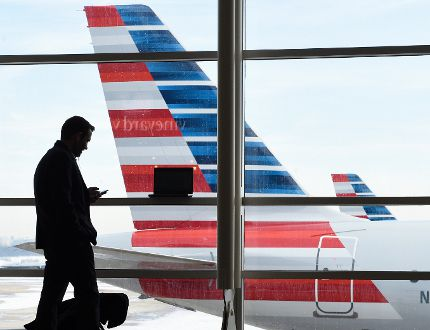 "In this Jan. 25, 2016, file photo, a passenger talks on the phone as American Airlines jets sit parked at their gates at Washington's Ronald Reagan National Airport. American Airlines announced Wednesday, Jan. 18, 2017, that passengers will be able to buy ""basic economy"" tickets starting in February that will be similar to bare-bones fares already offered by Delta Air Lines and soon to be matched by United Airlines. The basic-economy fares will have a lower price, but will offer fewer comforts. (AP Photo/Susan Walsh, File)"
