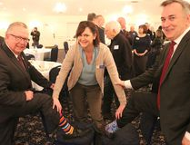 BRUCE BELL/THE INTELLIGENCER Prince Edward County Chamber of Tourism and Commerce executive director Emily Cowan checks the socks of Mayor Robert Quaiff (left) and Bay of Quinte MP Neil Ellis at Thursday morning's Breakfast Briefing with the Mayor at the Waring House. The two politicians have a standing joke about who wears the nicest socks.