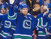 Canucks captain Henrik Sedin waves as he receives a standing ovation from his teammates on the bench and the crowd after scoring a goal against the Panthers to record his 1,000th career point during NHL action in Vancouver on Friday, Jan. 20, 2017. (Darryl Dyck/The Canadian Press)