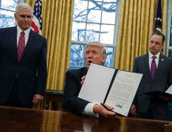 "In this Jan. 23, 2017, photo, Vice President Mike Pence, left, and White House Chief of Staff Reince Priebus watch as President Donald Trump shows off an executive order to withdraw the U.S. from the 12-nation Trans-Pacific Partnership trade pact agreed to under the Obama administration in the Oval Office of the White House in Washington. Trump's ""peace through strength"" could mean more U.S. military power in Asia, reassuring allies about America's resolve to counter China. That is, if they're still looking to Washington for reassurance. Trump called his speedy withdrawal from the Trans-Pacific Partnership a victory for American workers hurt by multilateral trade pacts. (AP Photo/Evan Vucci)"