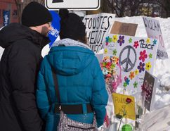 A couple stands in front of a makeshift memorial near the site of the mosque shooting, Tuesday, January 31, 2017 in Quebec City. (THE CANADIAN PRESS/Jacques Boissinot)