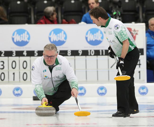 Skip Mike Harris watches a stone while lead Scott Foster gets set to sweep during the men's provincial curling championship in Cobourg, Ont., on Wednesday, Feb. 1, 2017. (Pete Fisher/Northumberland Today/Postmedia Network)