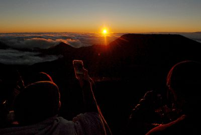 People watch as the sun rises in front of the summit of Haleakala volcano in Haleakala National Park on Hawaii's island of Maui, Sunday, Jan. 22, 2017. Reservations can be made up to two months in advance at the website recreation.gov. (AP Photo/Caleb Jones)