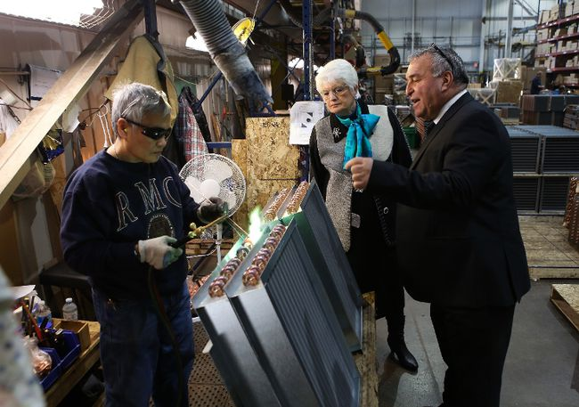 Pat Occhicone, president and chief executive officer of Direct Coil, and Treasury Board president Liz Sandals watch Edna Quintana weld during a tour of the factory, which on Friday announced plans for a $2.7M expansion. (Elliot Ferguson/The Whig-Standard)