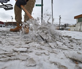 Scrapping compacted snow and ice on sidewalk along 107 Ave. in Edmonton, Saturday, February 4, 2017. Ed Kaiser/Postmedia