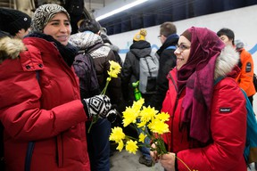 Nakita Valerio (right) with the Alberta Muslim Public Affairs Council, hands out flowers to women wearing hijabs at the University of Alberta LRT station, on Wednesday Dec. 7, 2016. The Edmonton police hate crimes unit has a suspect in custody following a Nov. 8 incident where a man threatened two Muslim women with a noose at the LRT station.