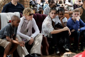 This file photo taken on April 2, 2013 shows US Pop Star Madonna (2nd L) sitting with her biological and adopted children (L to R) David Banda, Lourdes, Mercy James, and Rocco at Mkoko Primary School, one of the schools Madonna's Raising Malawi organization has built jointly with US organization BuildOn, during a visit in the region of Kasungu, central Malawi. A court in Malawi on February 7, 2017 approved Madonna's request to adopt two four-year-old twin girls, adding to the two other children that the US pop superstar adopted previously from the country. / AFP PHOTO / AMOS GUMULIRAAMOS GUMULIRA/AFP/Getty Images