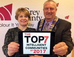 Grey County CAO Kim Wingrove and Warden Alan Barfoot hold up an image of the Top7 Intelligent Communities logo on an iPad following a Grey County council meeting Thursday in Owen Sound. (DENIS LANGLOIS/THE SUN TIMES)