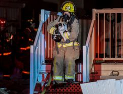 Sexsmith firefighter, Sheryl Braim rescues a frightened cat early Thursday morning after Sexsmith responded to a mutual aid call from the County of Grande Prairie Regional Fire Service for a structure fire in Clairmont around 3:30 a.m. A cat is being credited with alerting the family to the fire in the home. William Vavrek/Special to Daily Herald-Tribune