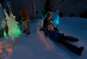 Kelly Davies is an ice carver who has taken leftover ice and created a 40-foot slide for his children Anna, 7 (r) and Julia,4, (m) and wife Kathy (l) taken on Thursday February 9, 2017 in Sherwood Park. Every year he has a new creation, but this is his biggest feat yet.  Greg  Southam / Postmedia