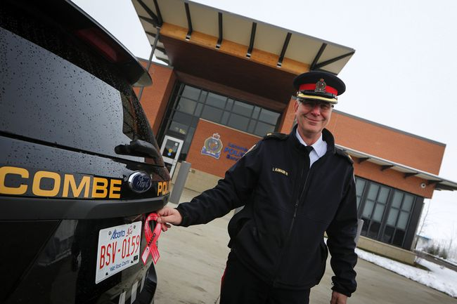 Lorne Blumhagen, the new Chief of Police for the Lacombe Police Service (LPS) places a MADD ribbon on a police cruiser last November. Blumhagen has been with LPS since 2014. (Ashli Barrett/Lacombe Globe)