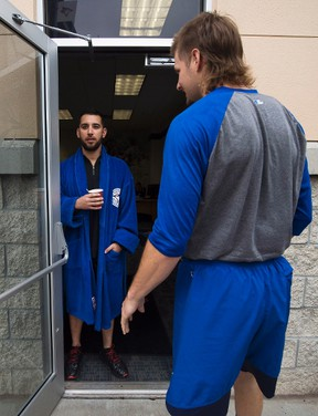 Toronto Blue Jays starting pitcher Marco Estrada, left, waits in his robe next to Matt Dermody as pitchers and catchers reported for their medicals in Dunedin, Fla., on Feb. 14, 2017. (THE CANADIAN PRESS/Nathan Denette)