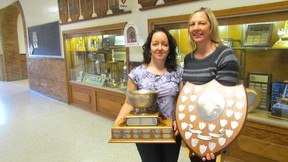 Laurie Webb, left, and Helen Crick, co-chairpersons of a committee collecting and documenting memorabilia from the former Sarnia Collegiate and St. Clair Secondary School, hold examples Tuesday next to the trophy case at the current location of Great Lakes Secondary School on Wellington Street in Sarnia. (Paul Morden/Sarnia Observer/Postmedia Network)