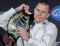 Welterweight champion Georges St. Pierre put his belt on his shoulder during a news conference in Montreal on January 23, 2013. (THE CANADIAN PRESS/Paul Chiasson)