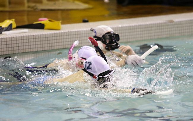 Underwater hockey players race from the edge of the pool to the puck, wearing snorkel gear and armed with sticks similar to those used in sledge hockey. (Ashli Barrett/Lacombe Globe)
