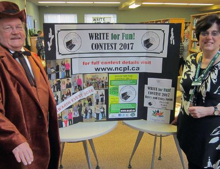 The ninth annual Write for Fun competition was launched Thursday at the Simcoe branch of the Norfolk Public Library. Master-of-ceremonies, at left, was Larry Dawson, who attended in his capacity as Norfolk's Canada 150 mascot John Charlton. At right is Norfolk Public Library CEO Heather King. MONTE SONNENBERG/SIMCOE REFORMER