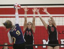 St. Marys defenders Aimee King (14) and Abi Versteegh try to get in front of Mia Valcke's smash during the Huron-Perth senior girls volleyball final Thursday at St. Marys. The Salukis beat the St. Mike's Warriors in four sets, but both teams advanced to their respective WOSSAA championships. Cory Smith/The Beacon Herald