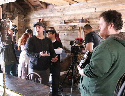 Sarnia-based director Aaron Huggett gives direction to crew members during the filming of a new Black Donnellys movie in Napier Friday. An 80-member cast and crew started work on the Eclipse Media production this weekend, filming scenes in an 1850s-era log cabin in Napier, as well as scenes in Lucan. Barbara Simpson/Sarnia Observer/Postmedia Network