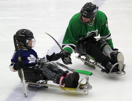 Sledge Hockey Manitoba player Jordan Danman (right) gives Sophie English, 6, one of the two pointed hockey sticks used to move along the ice. A sledge hockey demonstration was held at the Kenora Recreation Centre on Saturday, Feb. 18 as part of the Hockey Day in Canada festivities. Kathleen Charlebois/Daily Miner and News