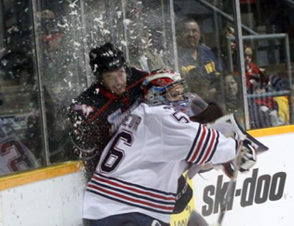 Owen Sound Attack centre Kevin Hancock (left) gets checked into the boards by Oshawa Generals goalie Jeremy Brodeur during first period Ontario Hockey League action on Saturday.